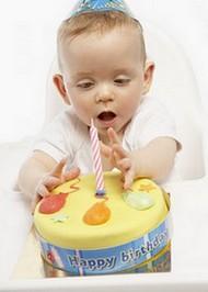 Малыш тянет руку к свечке в торте