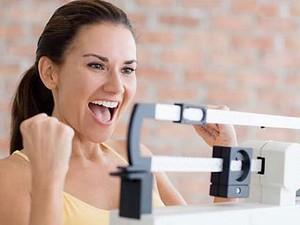 Девушка радуется, глядя на весы