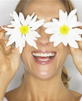Девушка держит два цветка перед глазами