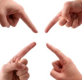 Четыре руки направляют указательные пальцы в одну точку