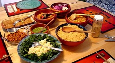 На столе много чашек с разнообразными продуктами