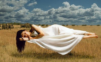 Спящая женщина, зависшая в воздухе над полем