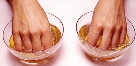Пальцы рук в двух чашках с жидкостью