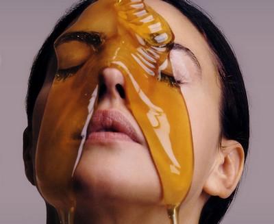 Девушке на лицо льется мёд
