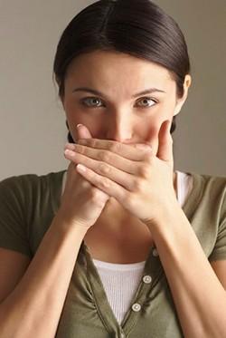 Девушка прикрывает руками свой рот