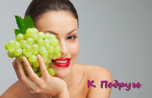Девушка держит в руке виноград